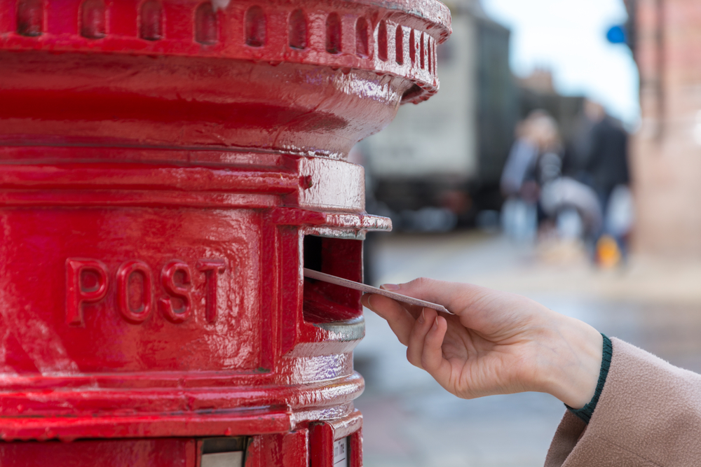 hand putting letter in red letterbox