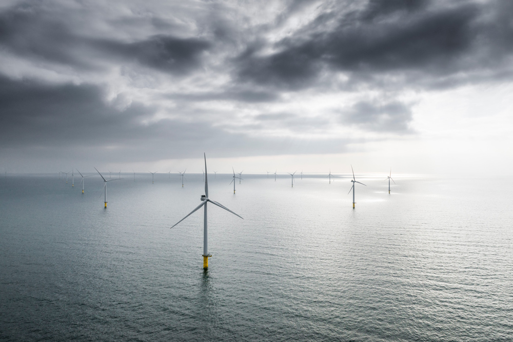 wide shot of Rampion 1 Wind Farm with atmospheric grey clouds
