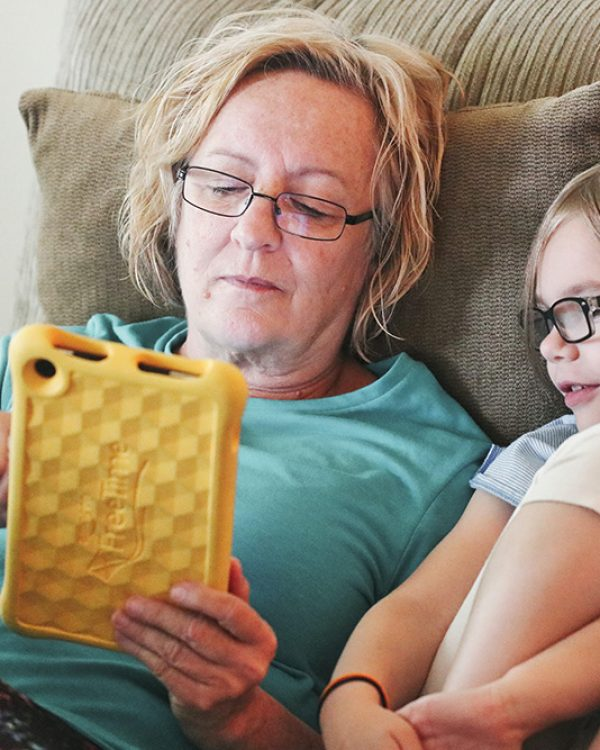 elderly lady using tablet with young girl